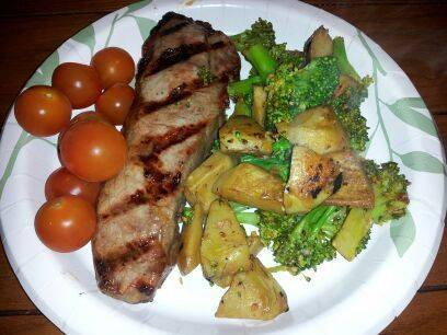 New York strip with tomatoes and garlic broccoli and artichoke hearts.