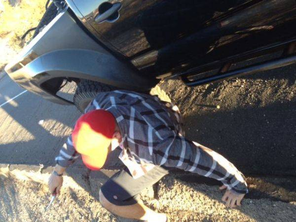 Eddie crawling around removing the zip ties I put on his drive shaft. lol